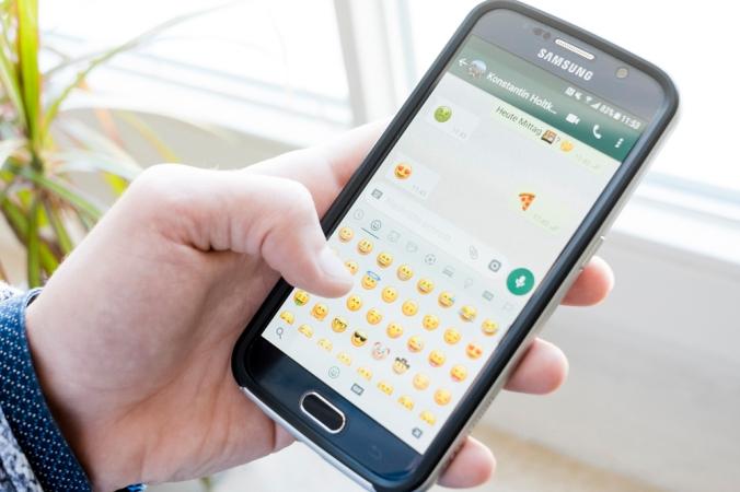 Smartphone mit Chat-Verlauf und Emojis